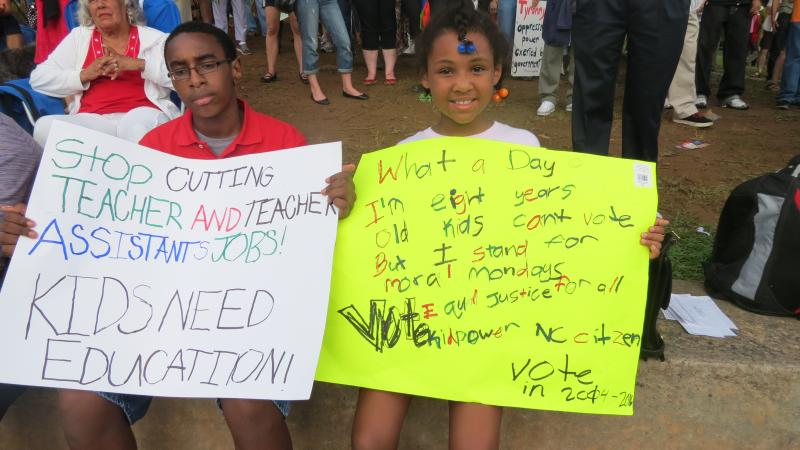 CMS students Andrew Shepherd, 11, and Delilah Pearson, 8 protesting teacher cuts at the Moral Monday in Charlotte. 'They're cutting [teachers] and they really shouldn't be,' Pearson says.