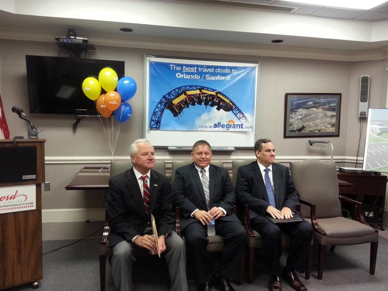 Concord Mayor Scott Padgett, Aviation Director Rick Cloutier and Cabarrus County Convention and Visitors Bureau EVP John Mills await the city's formal announcement of expanded service at Concord Regional Airport.