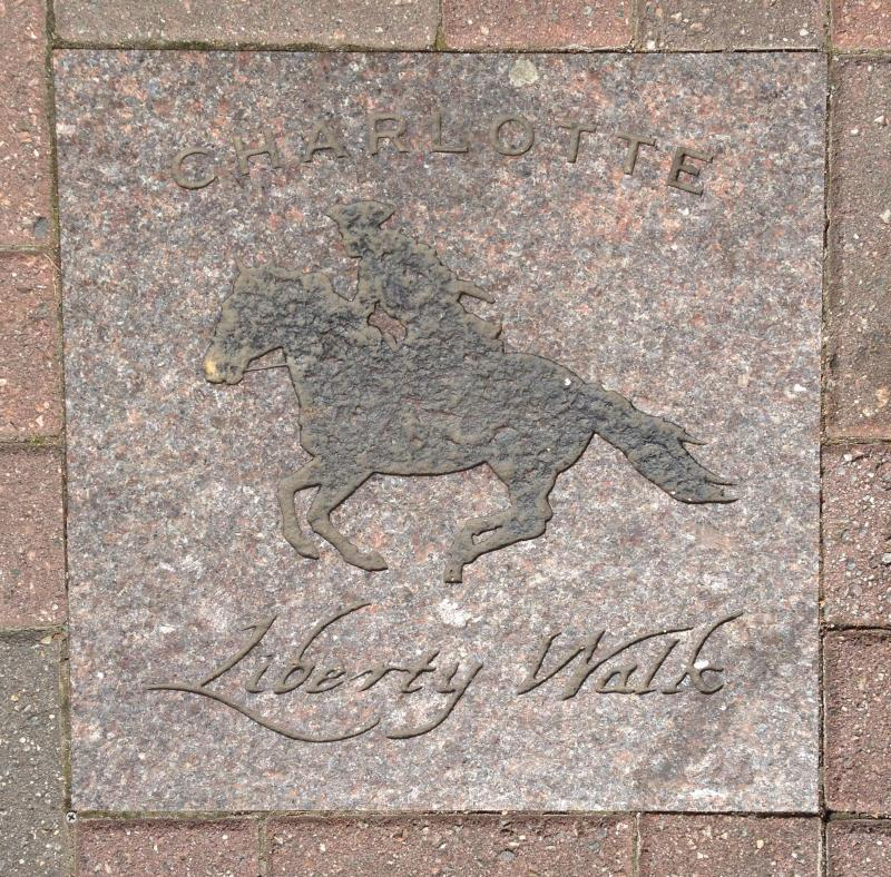 A marker for the Revolutionary War history Liberty Walk on an uptown sidewalk.