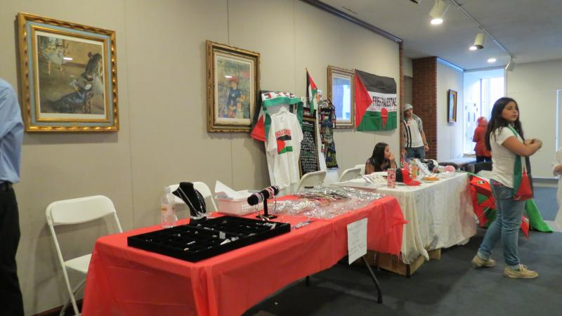 Outside the auditorium, local Palestinians sell oil from the olive trees in Nablus, t-shirts and jewelry.