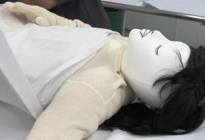 A sheet is wrapped around a female dummy to demonstrate the washing and shrouding process for a Muslim burial at the Islamic Society of Greater Charlotte.