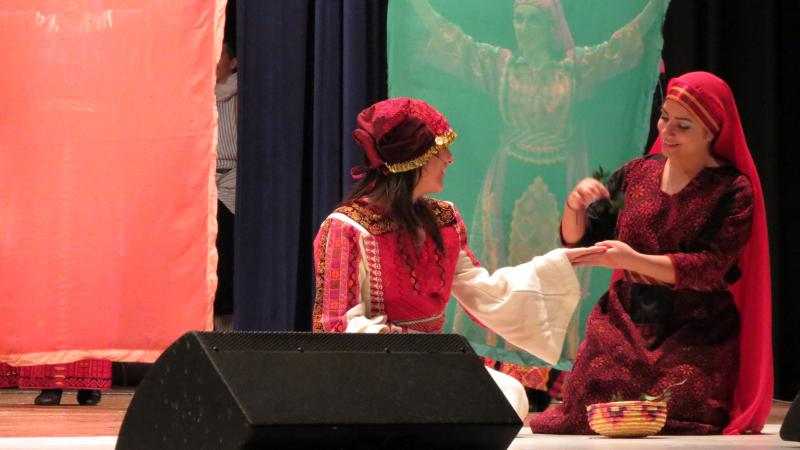 A dancer applies henna to a bride for her wedding.