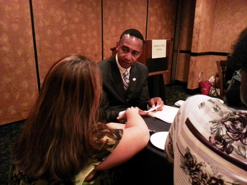 Democratic mayoral candidate Patrick Cannon chats with an attendee at a Queen Bees networking luncheon.