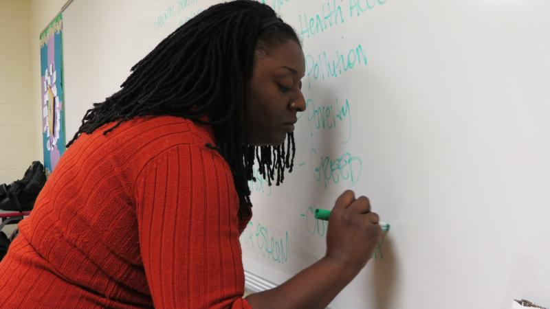 Starr Seward, the Sacrificial Poets' Program Coordinator, writes down 'problems of the world' on the whiteboard.