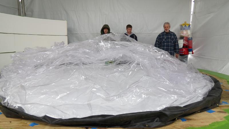 Workers inflate a Piedmont Natural Gas snow globe for the Thanksgiving Day Parade.