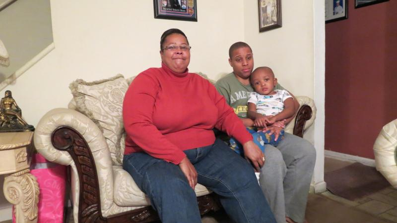Warren's mother, Elaine, sitting next to her son Damian and grandson Eli Kotay in the family's living room.