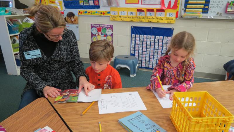 Parent volunteer Cheryl Mahoney helps a student read while he bounces on his ball.