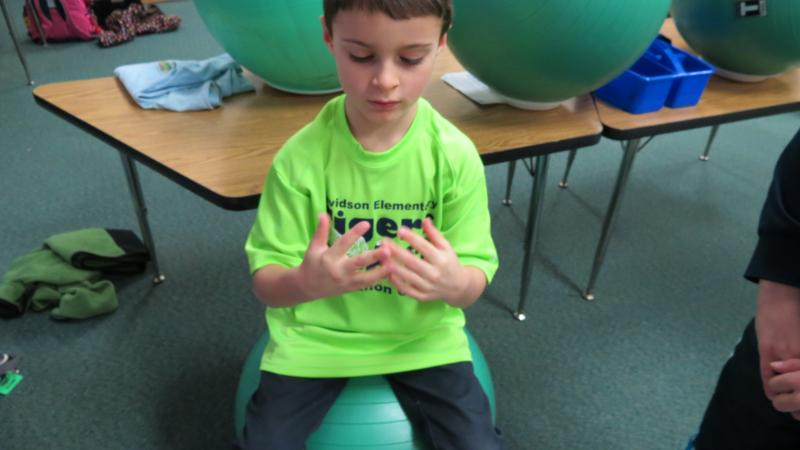 Seven-year-old Cowen Harris shows off his morning exercise routine with his stability ball.