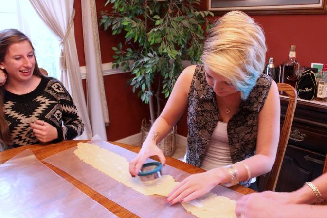 Taylor Mezger cuts out circles to assemble the pierogi while Sarah Hoffman waits to fill the pierogi.