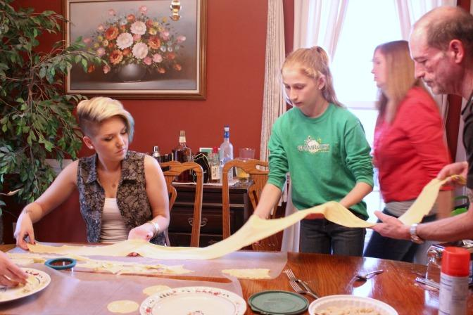 Family and friends assist with the sheet of pierogi dough. From left to right: Taylor Mezger, neighbor Kate Hoffman, Melissa Mezger, Ken Mezger.
