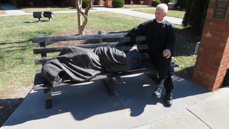 "Father David Buck of St. Alban's Episcopal Church sits next to ""Homeless Jesus."""