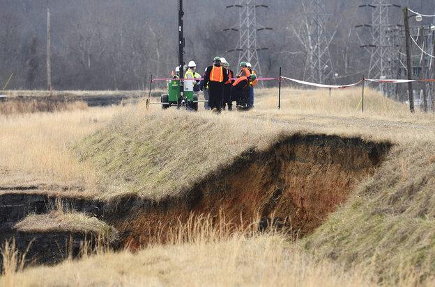 Officials examine the damage overlooking where a storm water pipe broke and coal ash from an unlined pond was released into the Dan River in Eden, NC.