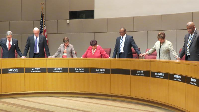 Charlotte city council members hold hands on Monday night while Councilman Al Austin says a prayer for the city before the meeting.
