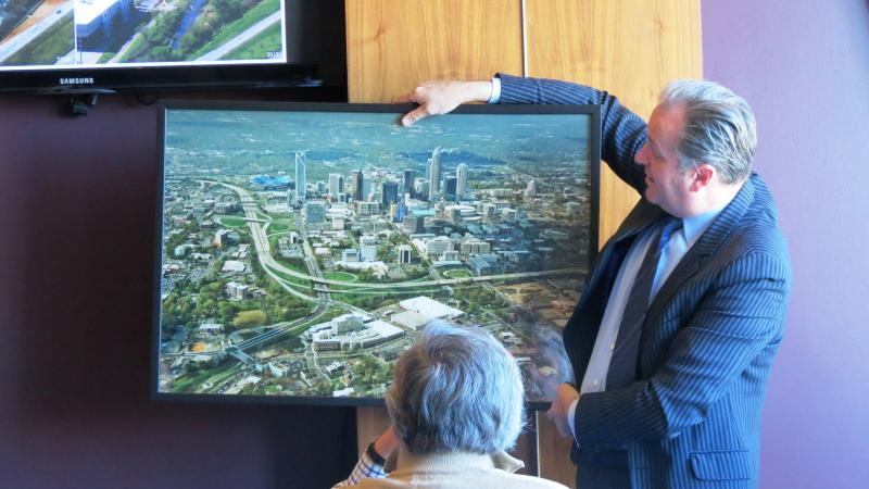 Roth shows off a photo of Charlotte in 2010. He says the Little Sugar Creek Greenway has become a destination for residents and visitors because of public investment.