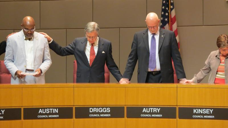 Charlotte city council members held hands on Monday night while Councilman Al Austin read a prayer for the city before the meeting.