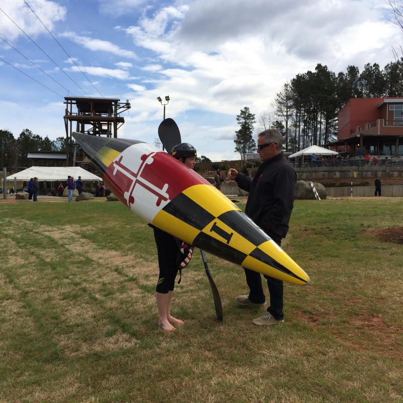 Ashley Nee holds her kayak with a Maryland flag design while talking to USA Canoe/Kayak CEO Joe Jacobi
