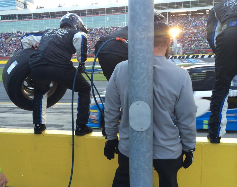 The pit crew gets ready to pounce off the wall as Kasey Kahne swerves onto pit road.