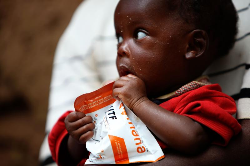 A child in Rwanda eats a packet of MANA.