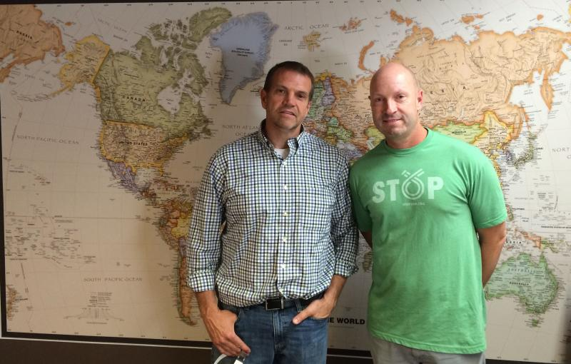 MANA's Mark Moore and Troy Hickerson stand in front of a map with dots marking countries where they send their product.