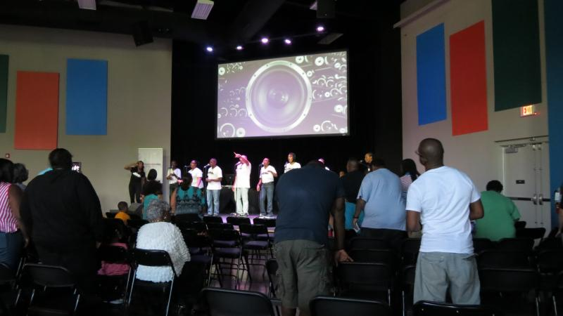 On the screen, visuals of a vibrating subwoofer accompany the hip-hop music during the praise and worship session.