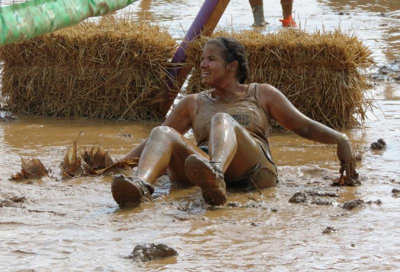 A member of the mud volleyball team, The Dirty Murphys, falls during a mud volleyball match.