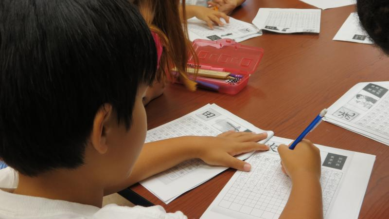 A student in the Chinese language summer camp at the Asian Library practices writing Chinese characters.