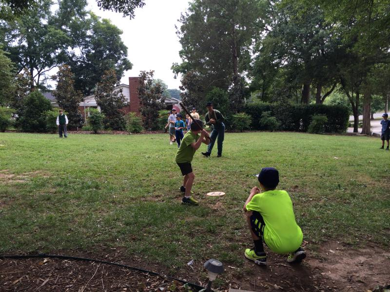 "The group plays ""rounders,"" a game similar to baseball from the 1860s."