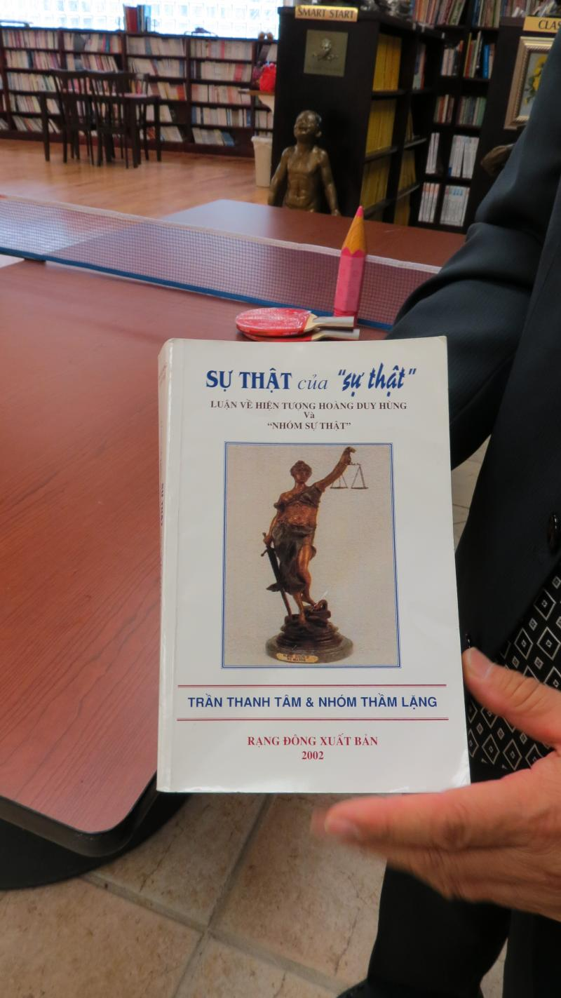 Ki-Hyun Chun shows off a book from the Vietnamese section of the library.