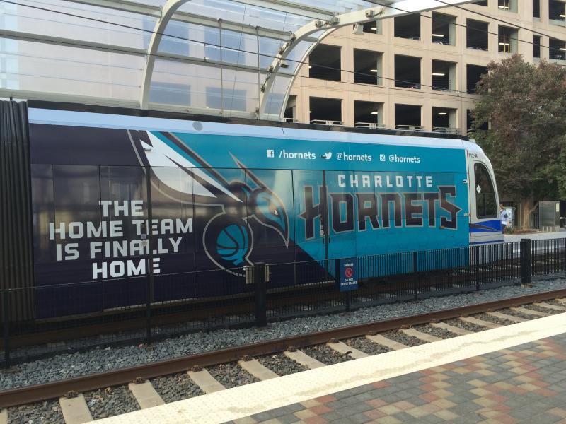 Hornets fans arrive near the arena on the light rail.