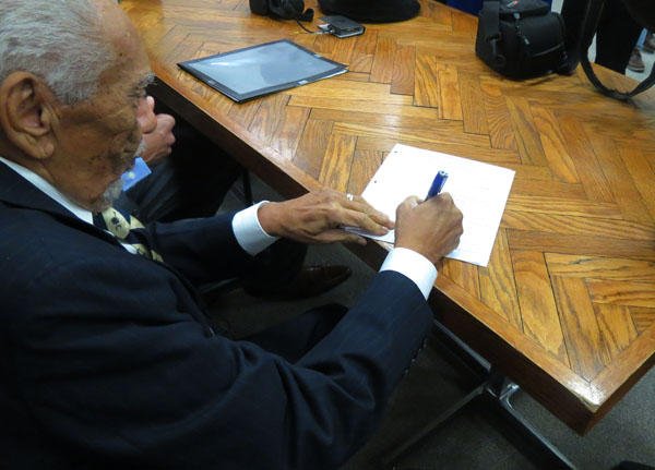Former SC Chief Justice Ernest Finney signs a court document before the hearing of the Friendship 9 in rock Hill,l SC. Finney represented the men 54 years ago.