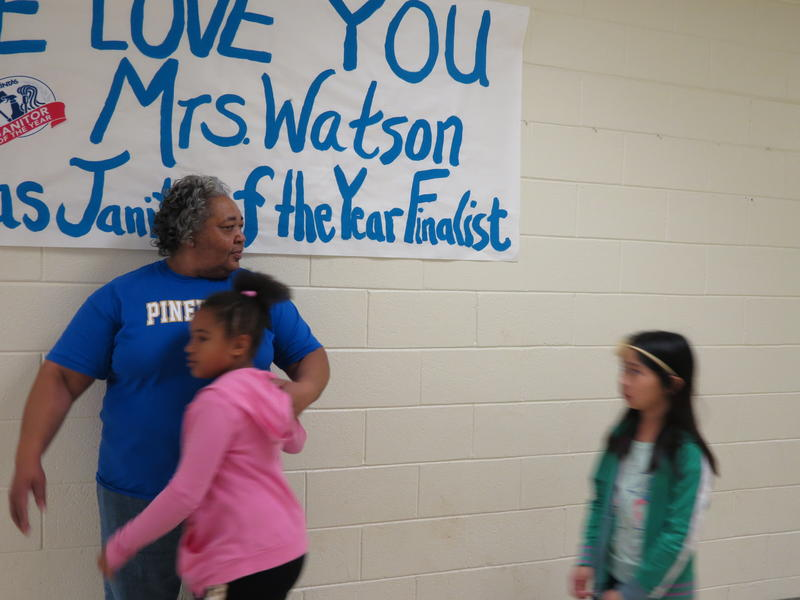 Barbara Watson ushers students to lunch. Behind her is a congratualtory sign for being a janitor of the year  finalist .