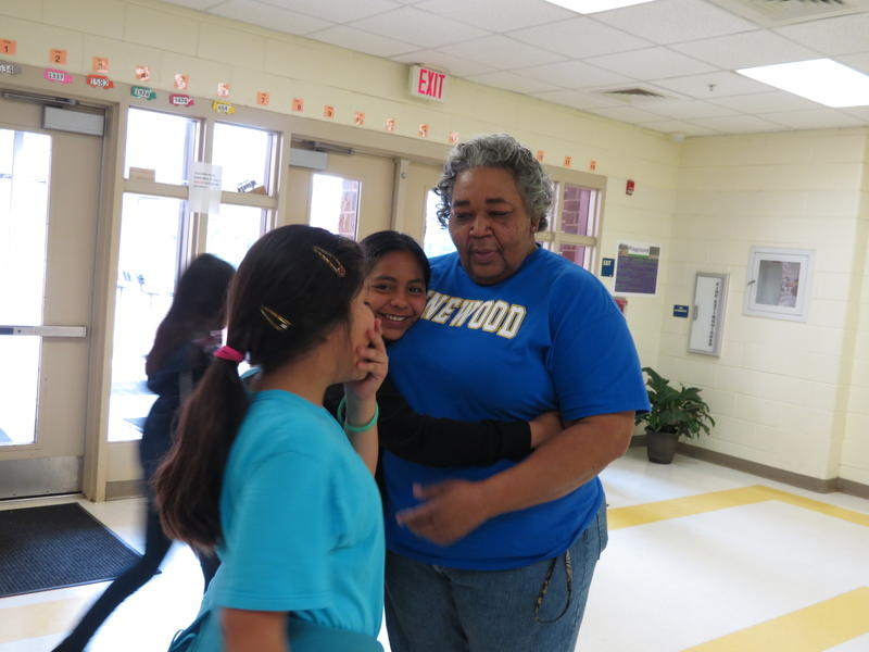 Pinewood Elementary custodian Barbara Watson gets a hug from a student as she talks to them about their day.