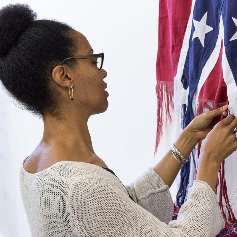 Sonya Clark unraveling the Confederate flag.