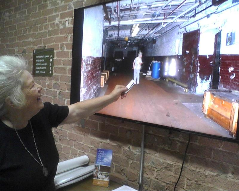 Lucy Penegar points to picture of herself in lobby slide show as she gave a tour of the Loray Mill before it was renovated