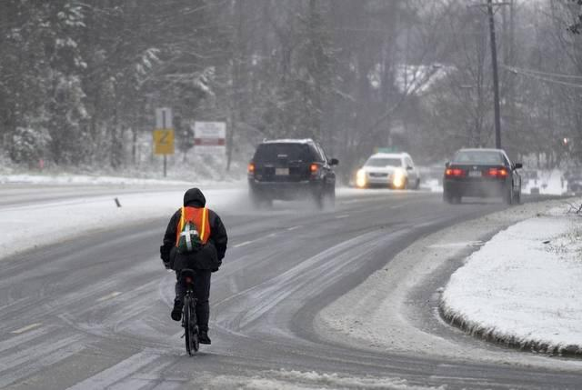 A cyclist pedals his way west on Mallard Creek Church Road near I-85. Overnight snow depths varied across the Charlotte region.