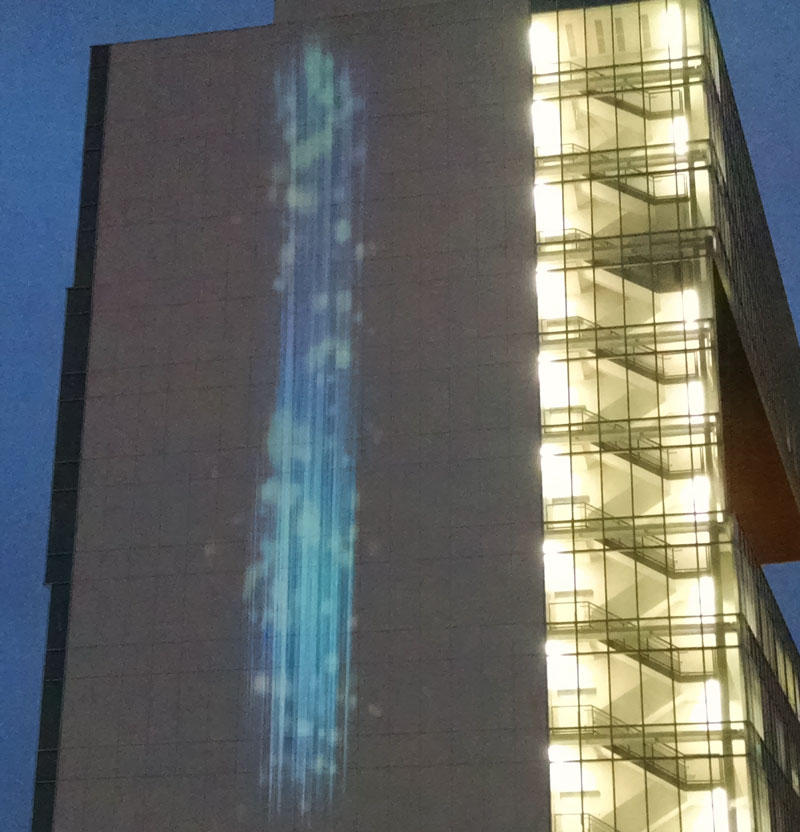 Yellow and orange spots sprinkle the blue waterfall as pollution in the air rises.