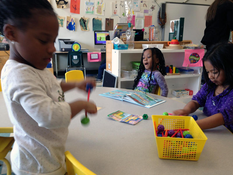 "Students in Cook's class choose their own activities like coloring, paging through books, and stacking blocks during ""center time."""