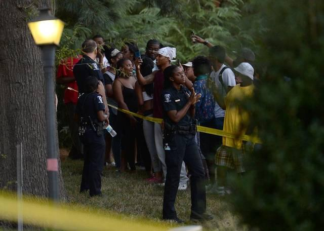 People gather on a hill as Charlotte police work the scene at The Village at College Downs apartments on Tuesday, September 20, 2016.