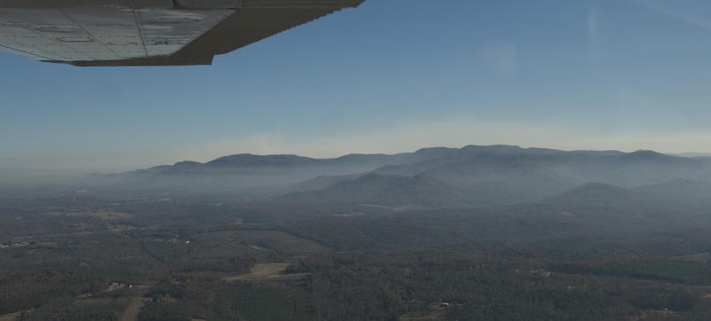 Smoke hangs on mountainsides and sits in valleys. The layer behind the mountains is from the Chimney Rock fire.