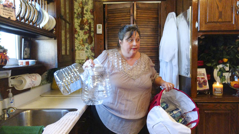 Deborah Graham holds an armful of plastic water bottles for recycling.