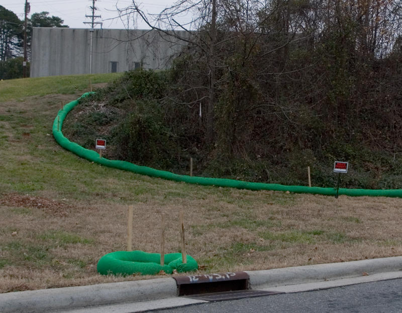 "Green ""filter socks"" are designed to control runoff behind the old Carolina Asbestos plant in Davidson.  The trees will be removed and the hill full of asbestos covered starting next week."
