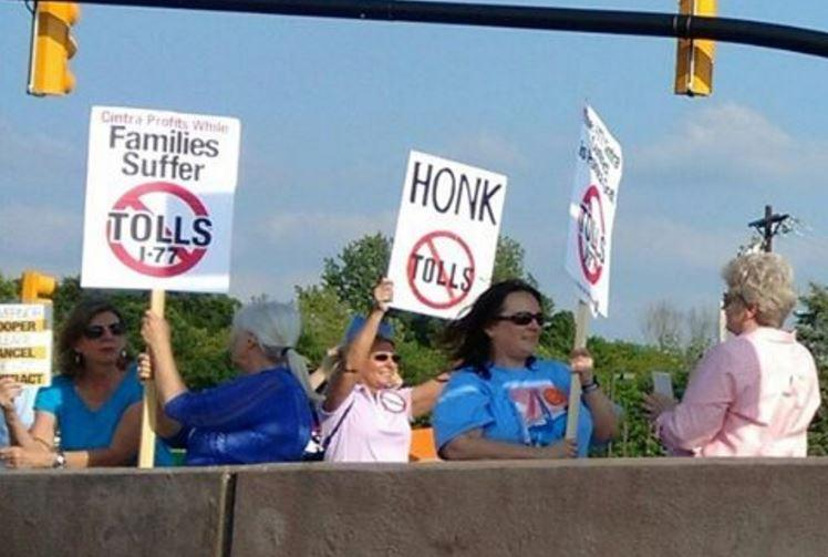 Toll opponents protested on the Exit 28 overpass in Cornelius Friday.