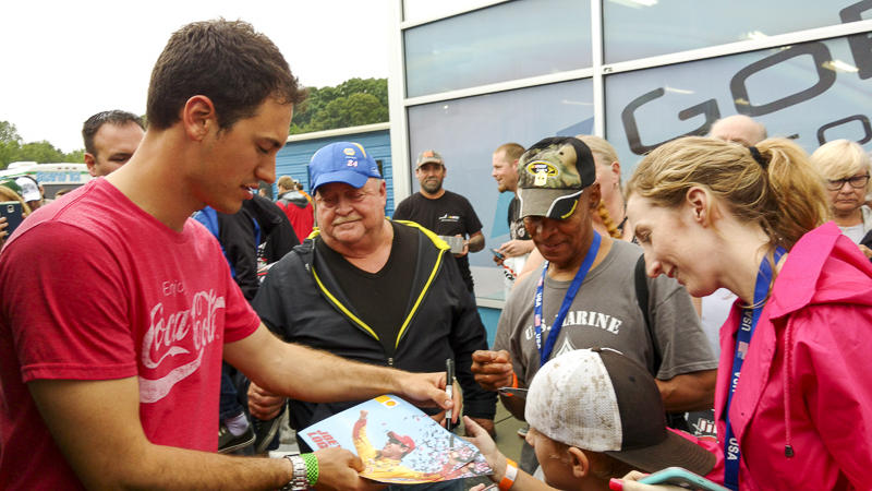 Joey Logano signs autographs during a break.