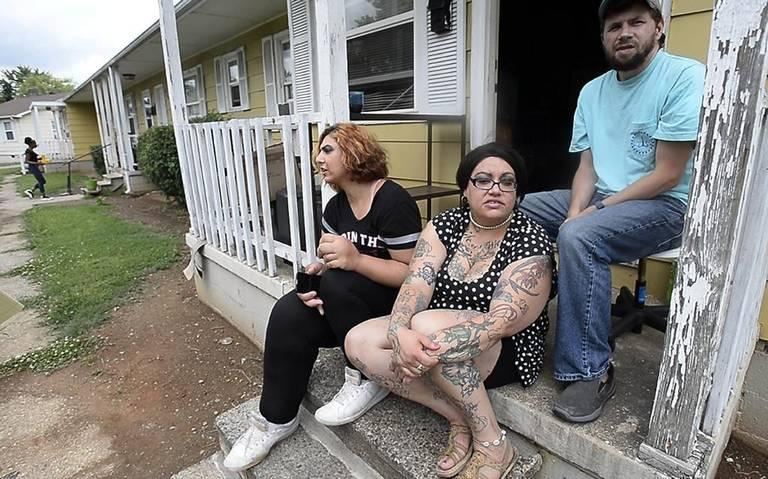 People who live in Brookhill Village, at South Tryon Street and Remount Road, are worried as they watch workers tear down parts of  the 67-year-old development all around them. Iya Jarouss, left, Cecillia Brunell, and Jeff Pegg sit on the front porch.