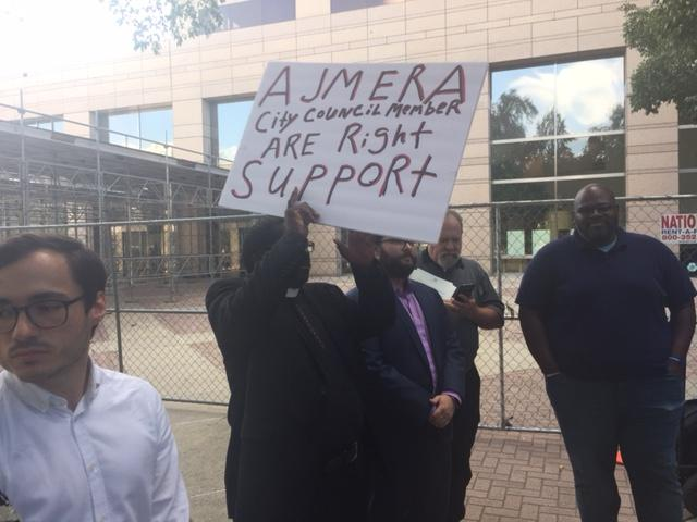 A supporter holds a sign for Dimple Ajmera.