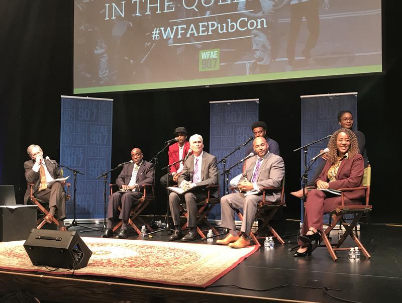 Panelists on stage, clockwise from left: Mike Collins, Greg Jackson, Robert Dawkins, Brenda Tindal, Vicki Foster, Patrick Graham, Patrick Mumford, Nicholas Wharton.