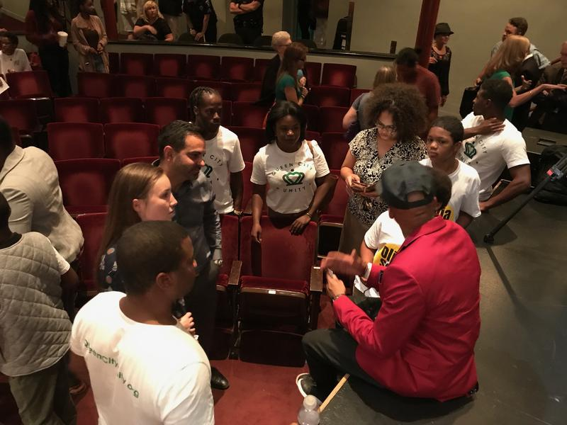 Greg Jackson, activist, founder of Heal Charlotte talks with members of the audience after the event.