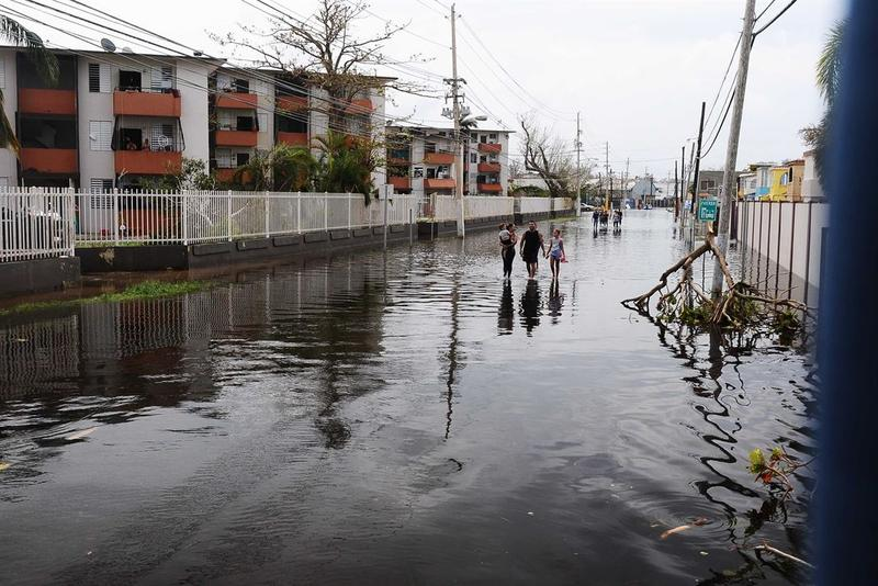 Puerto Rican residents walk in flooded streets in Condado, San Juan, Puerto Rico, Sept. 22, 2017, following Hurricane Maria