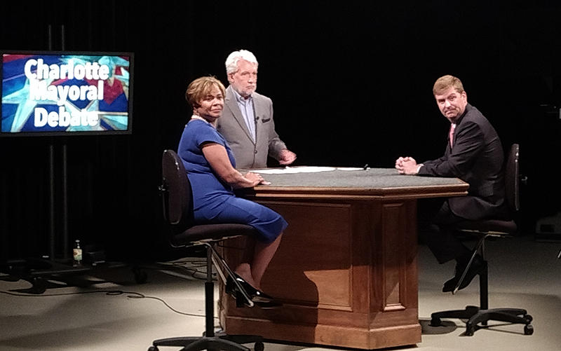 Moderator Jeff Sonnier of WTVI (center) and mayoral candidates Vi Lyles and Kenny Smith watched a video clip during the debate taping Thursday. The debate airs Tuesday night on WTVI.