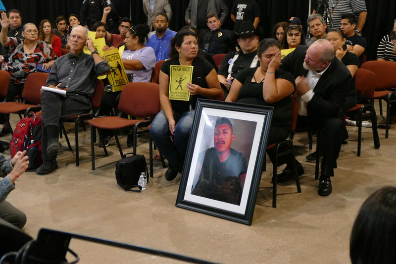 Azusena Zamorano attended Thursday's event with a portrait of her longtime partner, Reuben Galindo, who was fatally shot by CMPD officers in September.